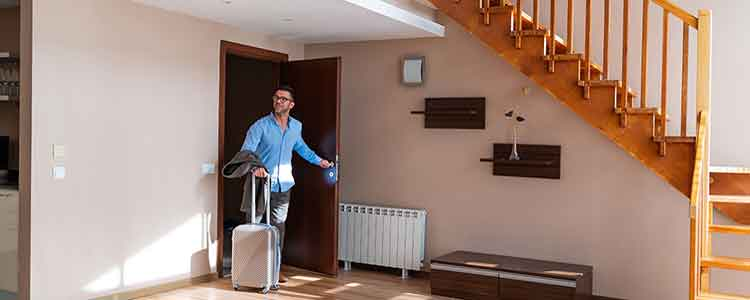 guest with luggage enters short-term rental